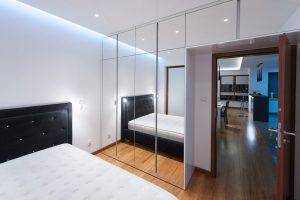 Sypialnia z zabudową ściany z przeszklonymi drzwiami