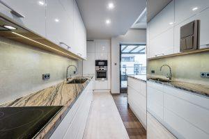 Duża biała kuchnia w kształcie litery U, otwarta na salon