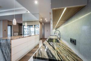 Kuchnia otwarta na salon z marmurowymi blatami