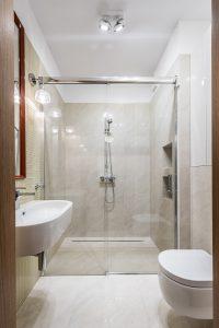Łazienka z prysznicem we wnęce, z odpływem liniowym i przesuwnymi drzwiami