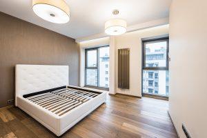 Nowoczesna sypialnia z łóżkiem małżeńskim z wysokim zagłówkiem i designerskim grzejnikiem