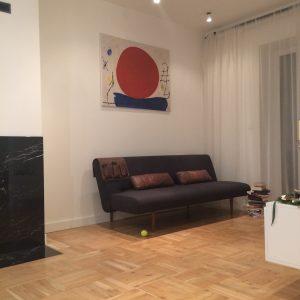 Salon z sofą i tv oraz drewnianą podłogą