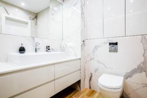 Biała łazienka w marmurze z meblami z lakierowanymi frontami