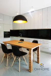 Biało-czarna kuchnia z drewnianym stołem i wiszącą lampą
