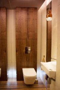 Łazienka z płytkami w kolorze drewna i podświetleniami