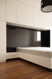 Nowoczesna biało-czarna sypialnia z zabudową ściany w wezgłowiu