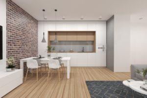 Biały aneks kuchenny z wstawkami drewnianymi i ceglaną ścianą