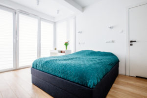 Minimalistyczna sypialnia z dużym tapicerowanym łóżkiem i toaletką