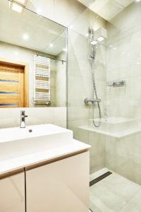 Biała łazienka z umywalką nablatową i prysznicem z odpływem liniowym
