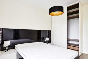 Biało-czarna sypialnia z szafą garderobianą