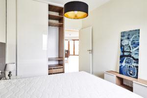 Jasna sypialnia z zabudową na wymiar pod telewizor
